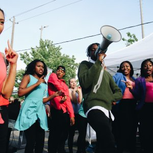 One teen dancing and another teen speaking into a megaphone.