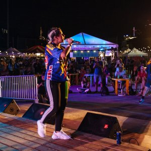 Singer standing on a stage holding a mic performing for a crowd a the patio