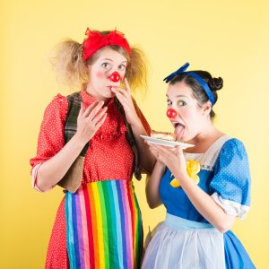 Two clowns licking their fingers after eating cupcakes