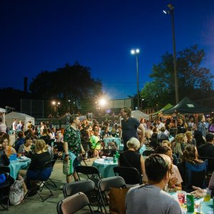Hundreds of festival goers sit at tables on the Fringe Patio in 2017