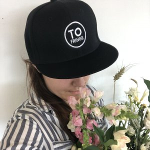 A person with long hair in a braid wearing a Fringe T.O. flat-brimmed black cap, holding a bouquet of flowers.