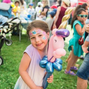 Young child enjoying the KidsFest Club and holding a balloon animal unicorn