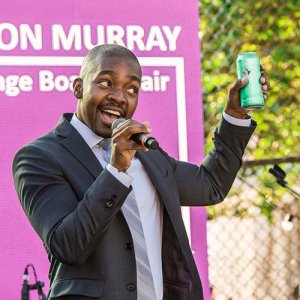 Jason Murray raises a Steam Whistle can and speaking into a microphone