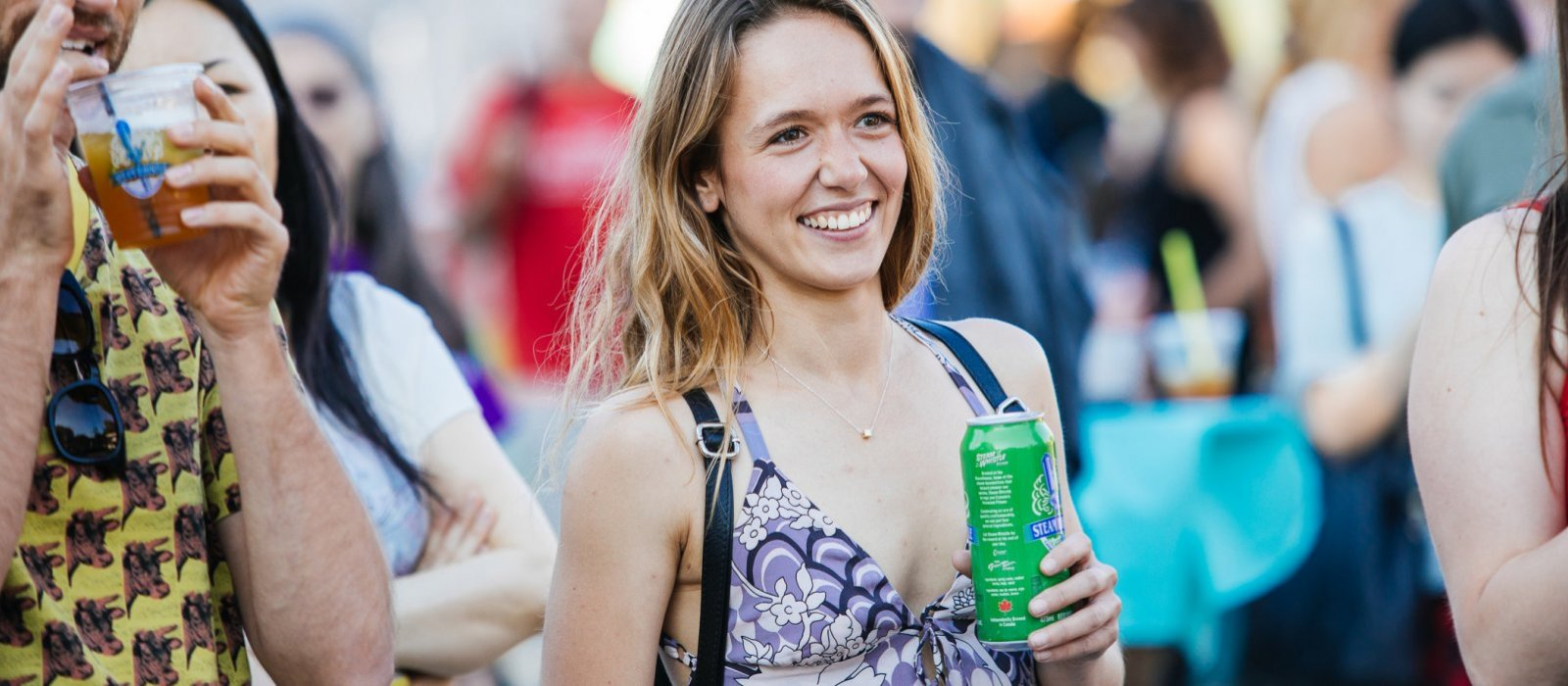A young woman enjoys a Steam Whistle beer at the patio