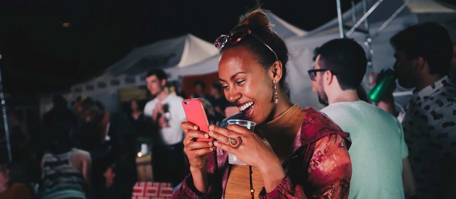 Fringe patron smiling and looking at cell phone