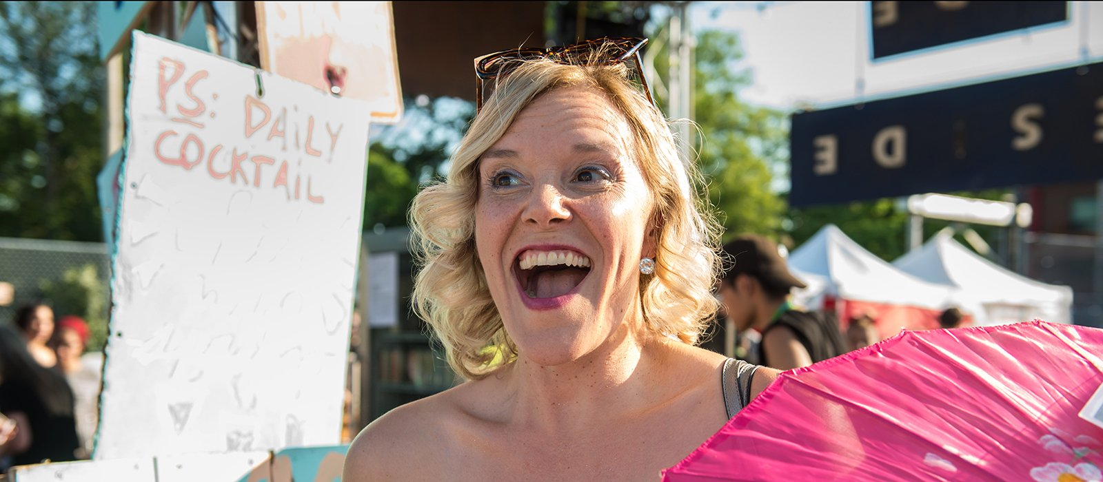 A fringe artist is seen smiling excitedly in the sunshine at the patio festival