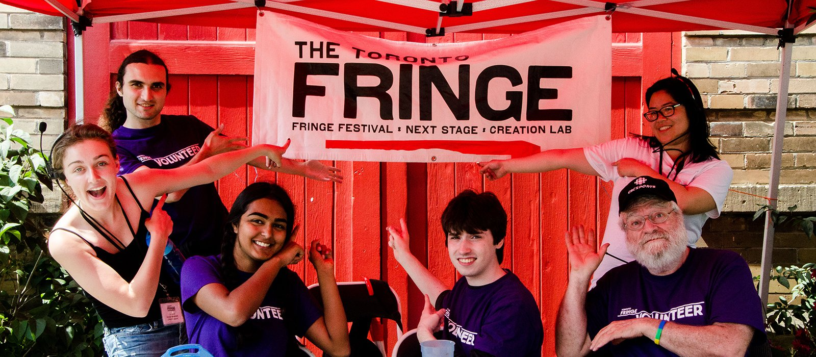 A handful of Fringe Staff and Volunteers hang out and point to the Fringe banner under a tent