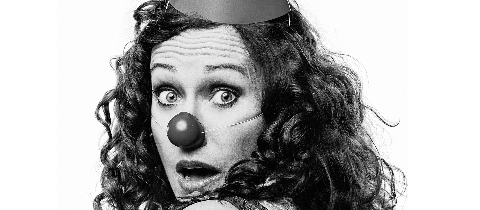 A performer from The Surprise looks back startled wearing a clown nose and party hat