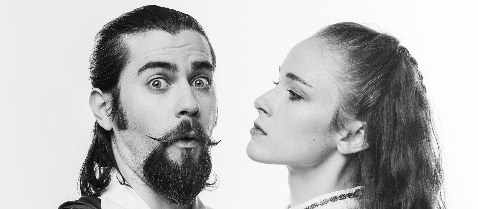 Two performers from the show Swordplay. A man with a waxed mustache and goatee looks with open eyes towards the camera while a woman stares at him very closely