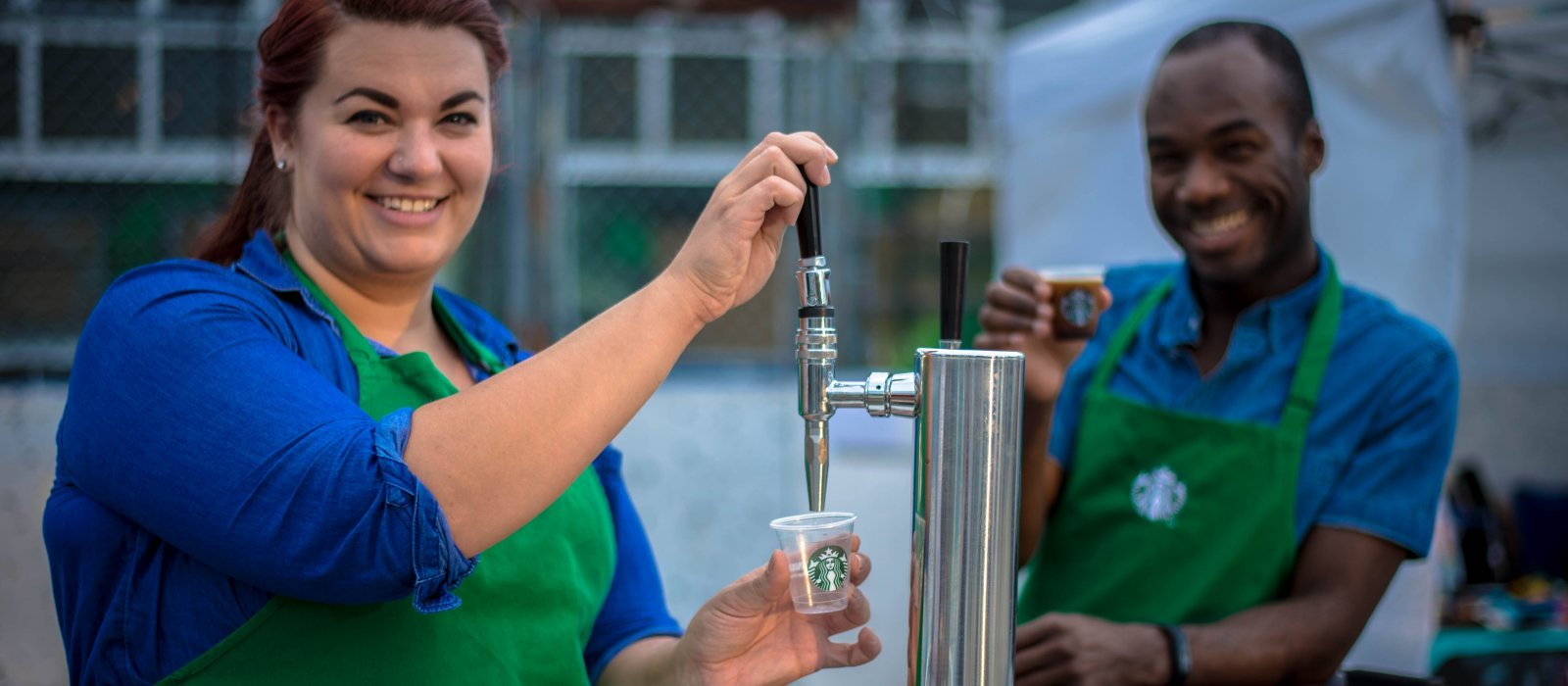Two Starbucks employees giving out samples at the Fringe patio